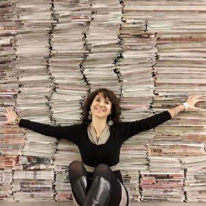 un ritratto di Lucia Tilde Ingrosso davanti una pila di giornali